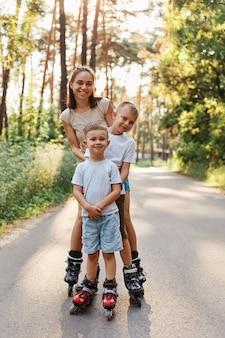 Família feliz, mulher de cabelos escuros, vestindo traje casual em pé com seus filhos ao ar livre, mãe com crianças patinando no parque na estrada de asfalto, se divertindo juntos.