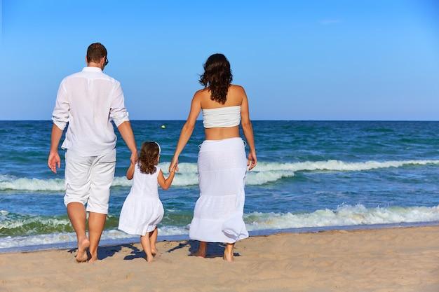 Família feliz na areia da praia andando na parte traseira