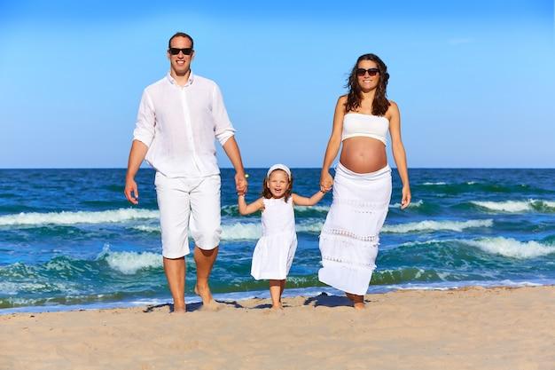 Família feliz na areia da praia caminhando