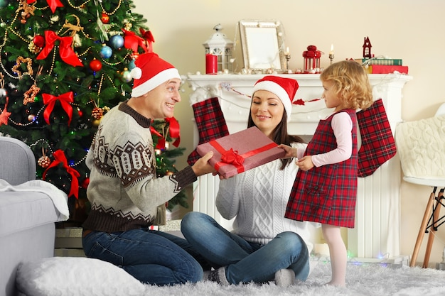 Família feliz na árvore de natal. dia de desembalagem