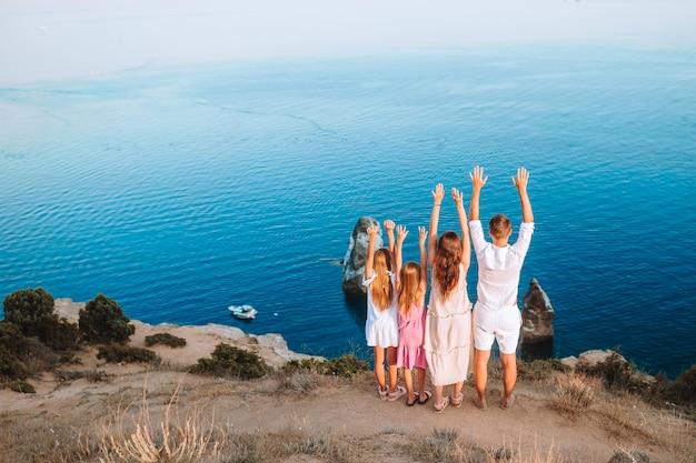 Família feliz na beira do penhasco apreciar a vista sobre a rocha no topo da montanha