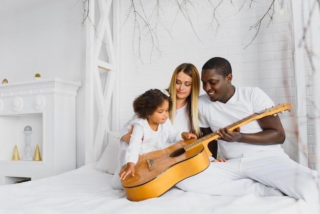 Família feliz na cama com um violão