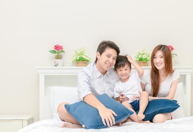 Família feliz na cama no quarto