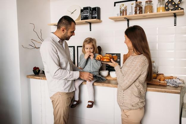 Família feliz na cozinha comendo croissants