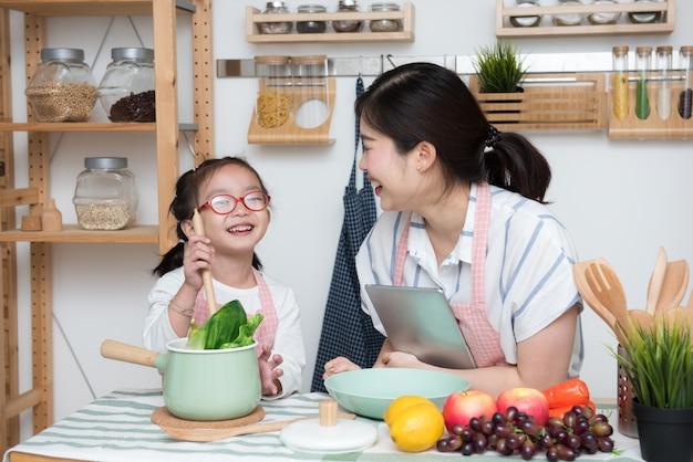 Família feliz na cozinha. filha de mãe e filho a preparar a comida.