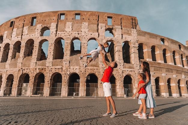 Família feliz na europa. pais e filhos em roma sobre o coliseu