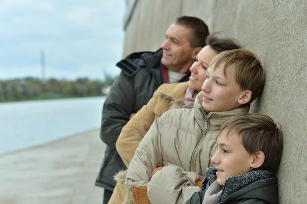 Família feliz na margem do rio no outono