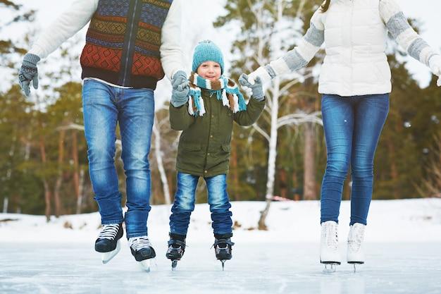 Família feliz na pista de gelo