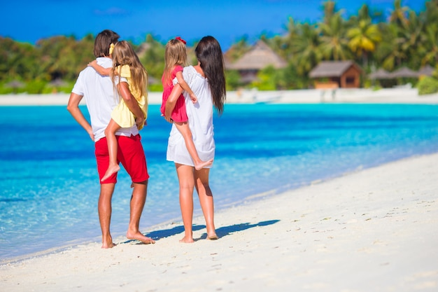 Família feliz na praia branca durante as férias de verão