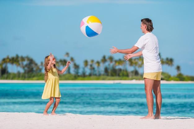 Família feliz na praia com bola se divertindo juntos