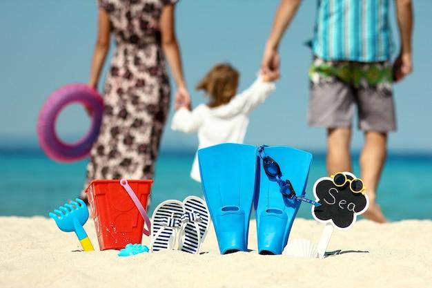 Família feliz na praia com nadadeiras e brinquedos