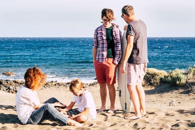Família feliz na praia com uma criança e um adolescente com prancha de surf com o mar ao fundo - criança e mãe brincando com a areia no chão