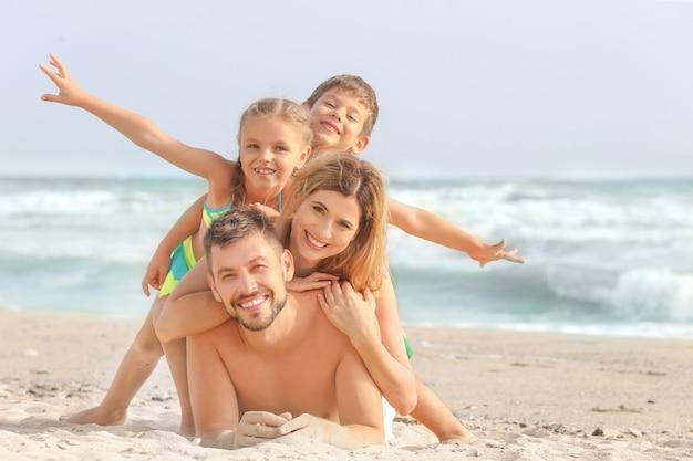 Família feliz na praia do mar no resort