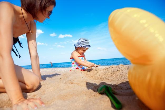 Família feliz na praia. mãe e filha no mar