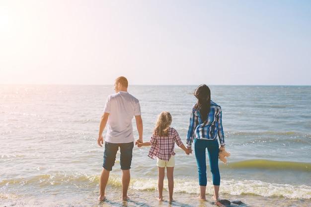 Família feliz na praia. pessoas se divertindo nas férias de verão. pai, mãe e filho contra o fundo azul do mar e céu. conceito de viagens de férias