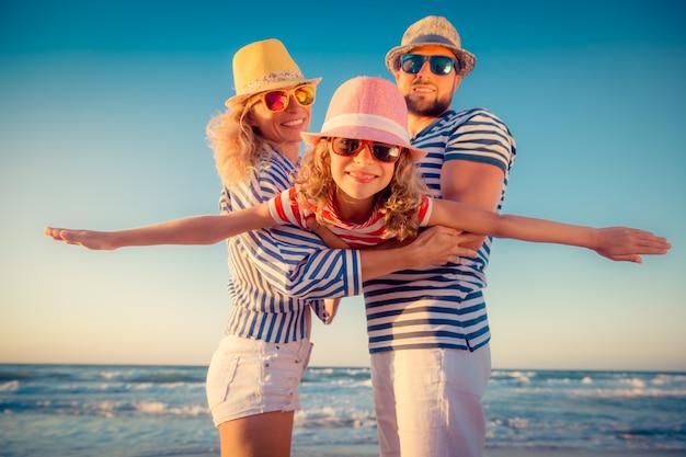 Família feliz na praia. pessoas se divertindo nas férias de verão. pai, mãe e filho contra o fundo do mar e do céu azul. conceito de viagens de férias