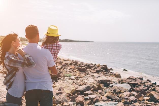Família feliz na praia. pessoas se divertindo nas férias de verão. pai, mãe e filho contra o mar azul e o céu. viagens de férias.