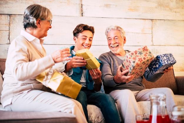 Família feliz na véspera de natal com avós e neto se divertindo com a troca de presentes