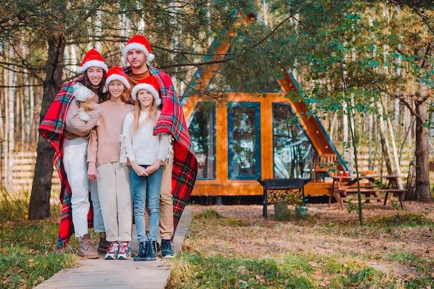 Família feliz nas férias de natal. pai com filhos enrolados em um cobertor