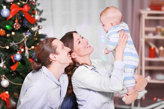 Família feliz no chão da sala decorada de natal