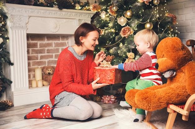 Família feliz no interior da casa no fundo da árvore de natal com presentes