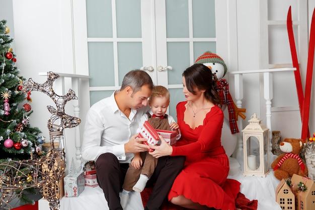 Família feliz no interior de casa no fundo da árvore de natal com presentes. feriados de ano novo.