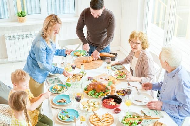 Família feliz no jantar na luz solar