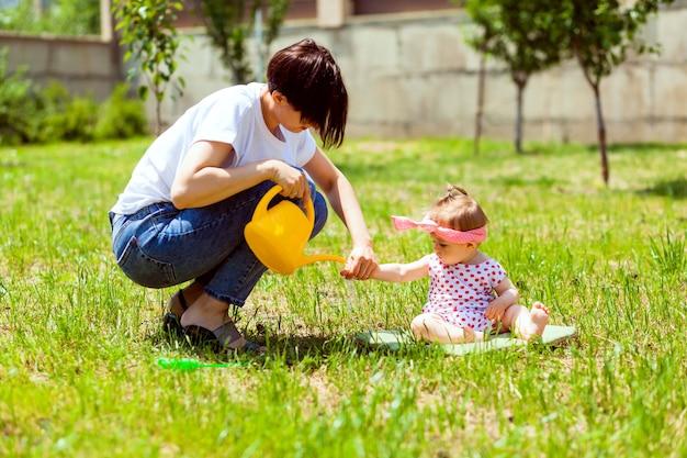 Família feliz no jardim. a água de um regador é derramada nas mãos da criança. mãe lava as mãos de um regador amarelo para uma criança no jardim.
