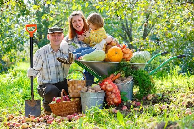 Família feliz no jardim com uma safra de legumes e frutas