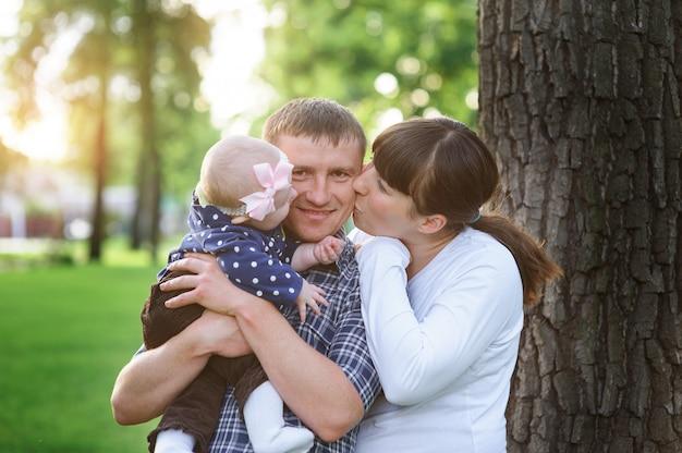 Família feliz no parque no dia ensolarado de primavera beijando o papai