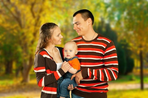 Família feliz no parque outono, aproveitando seu tempo
