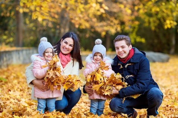 Família feliz no parque outono. mãe, pai e duas filhas na natureza.