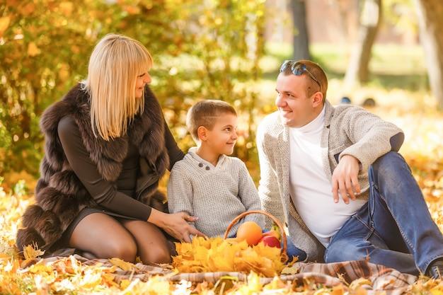 Família feliz no parque outono. piquenique
