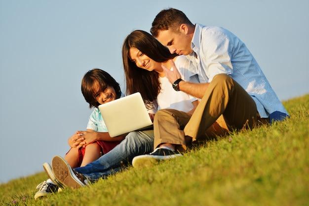 Família feliz no prado de verão bonito tendo tempo feliz aprendendo no laptop