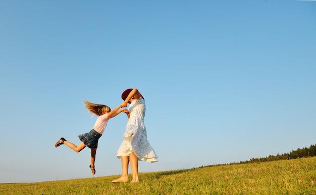 Família feliz no prado de verão bonito tendo tempo feliz circlin ao redor
