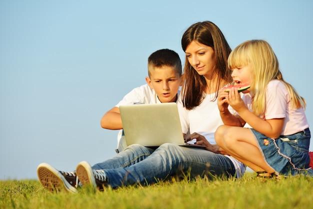 Família feliz no prado de verão bonito tendo tempo feliz com laptop