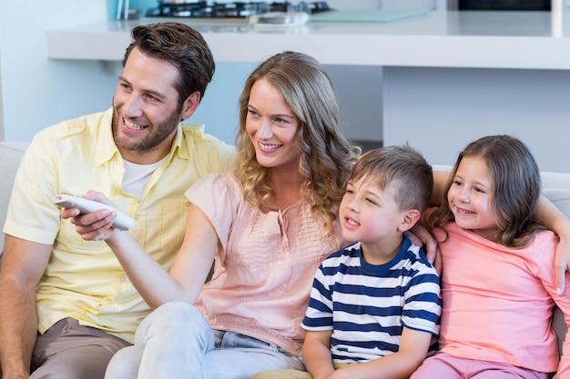 Família feliz no sofá assistindo tv