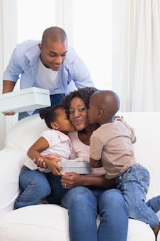 Família feliz no sofá dando presentes mãe