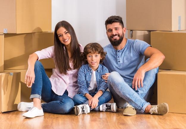 Família feliz nova que move-se para uma casa nova, abrindo caixas.