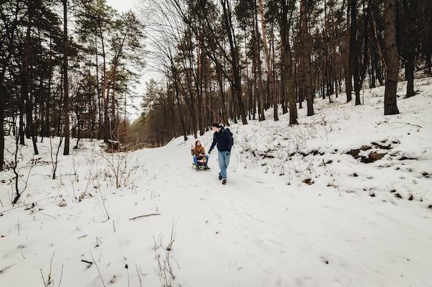 Família feliz: o homem carrega o trenó de madeira com a garota no trenó caminhando ao ar livre da floresta. caminhando no fim de semana de férias no parque de inverno.