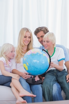 Família feliz olhando o globo no sofá