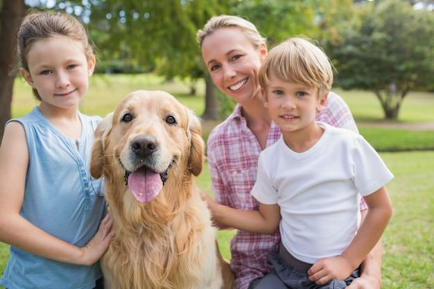 Família feliz olhando para a câmera e brincando com seu cachorro