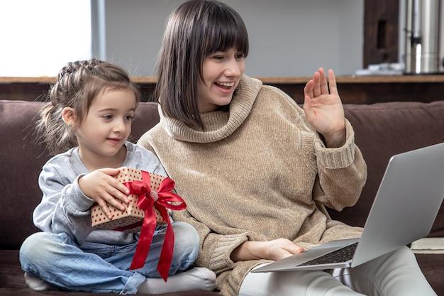 Família feliz olhando para a tela do laptop faz videochamada à distância. sorrindo, mãe e filha com caixa de presente, falando com a webcam.