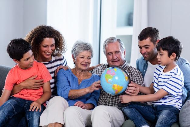 Família feliz, olhando para um globo na sala de estar