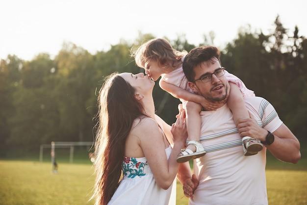 Família feliz, pai da mãe e filha do bebê na natureza ao pôr do sol