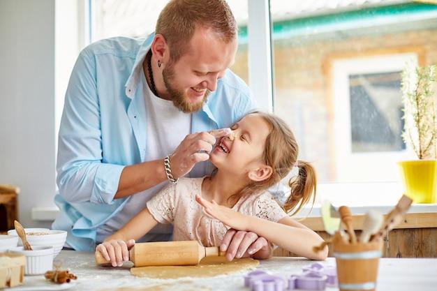 Família feliz, pai e filha abrem massa de biscoito na cozinha de casa