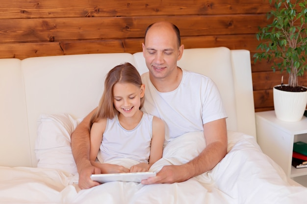 Família feliz, pai e filha conversando sobre o tablet em casa na cama. ensino à distância.