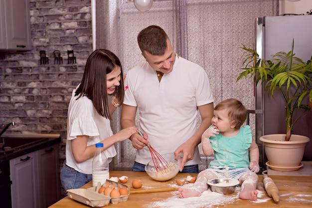 Família feliz, pai, mãe e filha brincam e cozinham na cozinha, amassam a massa e assam biscoitos.