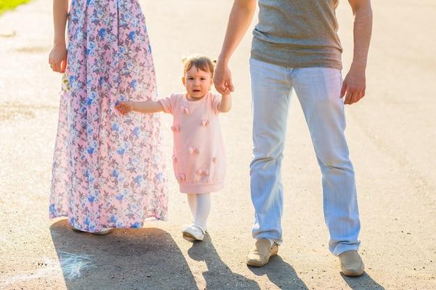 Família feliz, pai, mãe e filha de mãos dadas.