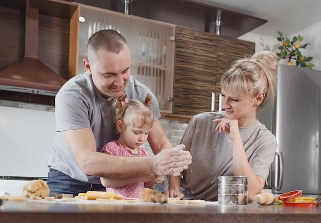 Família feliz, pai, mãe e filha juntos preparam deliciosos biscoitos de páscoa na cozinha de casa. preparação para férias em família